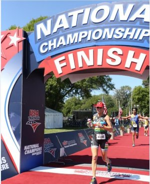 Lora crossing the finish line at USAT Nationals, all smiles of course.